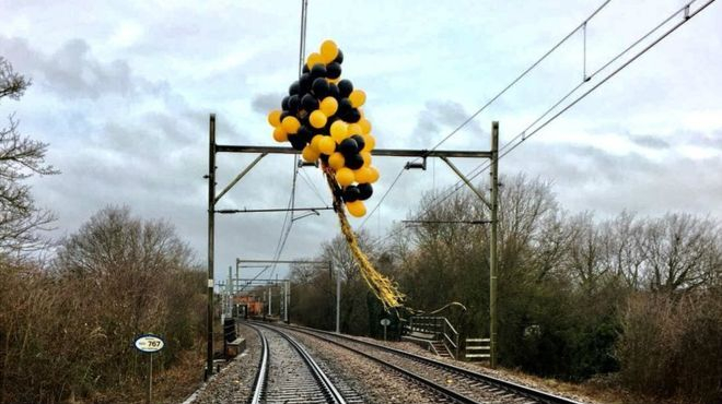 balloons tangled in overhead train lines